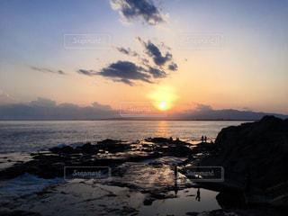 海に沈む夕日と人々のシルエットの写真・画像素材[1268654]