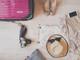 ピンクのスーツケースと服とカバンとパンプスと一眼レフカメラの置き画、フラットレイの写真・画像素材[1486429]