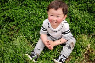 芝生に座っている小さな男の子 - No.1185772