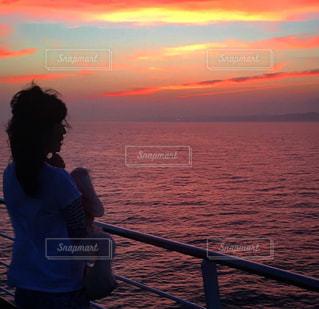 甲板で夕陽に染まる海と空に包まれました⋯の写真・画像素材[2157677]