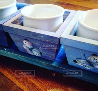 ちっちゃな白木の木製プランター。優しいブルーとパープルを塗って、蝶々を飛ばしました。の写真・画像素材[2173001]