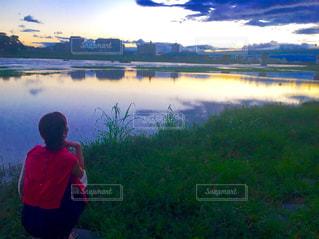 水の体の前に立っている男の写真・画像素材[1271115]