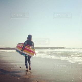 ビーチの上を歩くサーフボードを運ぶ人の写真・画像素材[1004416]