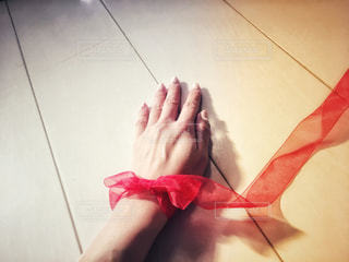 赤いリボンで結ばれる手の写真・画像素材[1021793]