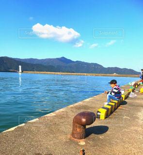 水の体の前に座っている人々 のグループの写真・画像素材[1321328]