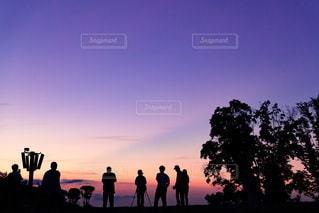 夕日の前に立っている人々のグループの写真・画像素材[3450312]