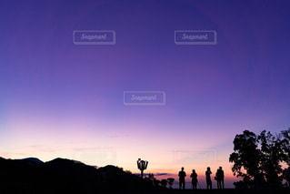 夕日の前に立っている人々のグループの写真・画像素材[3450310]