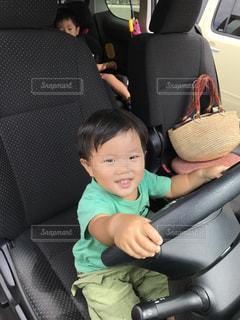 車の座席に座って運転ごっこする少年の写真・画像素材[1158818]
