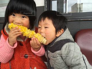 焼きとうもろこしを食べる姉弟の写真・画像素材[1009832]