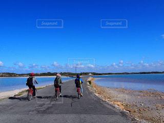 水の体の近くのビーチの上を歩く人々 のグループ - No.1016894