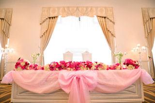 部屋の椅子にピンクの花の写真・画像素材[1229727]