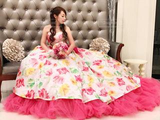 ベッドの上に座っている赤いドレスを着た女性の写真・画像素材[1233022]
