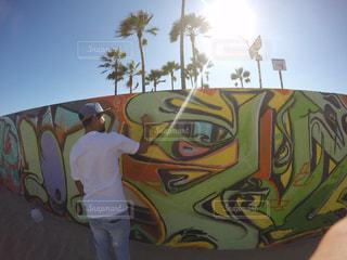 覆われている落書きの壁の前に立っている男の写真・画像素材[1008403]