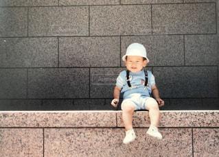 タイル張りの床に座っている男の子の写真・画像素材[1163657]