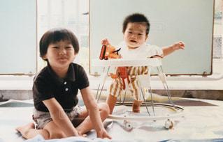 テーブルの上に座って若い男の子の写真・画像素材[1174510]