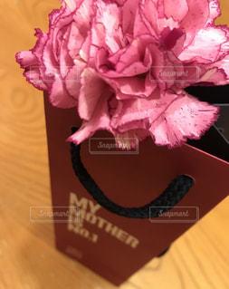 木製テーブルの上のピンクの花の写真・画像素材[1178929]