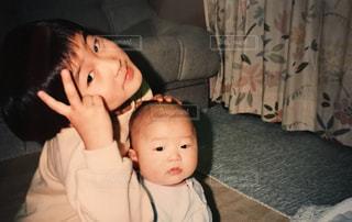 赤ん坊を保持ダウン横たわっている少年の写真・画像素材[1180565]