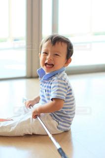窓の前で座っている男の子の写真・画像素材[1017996]