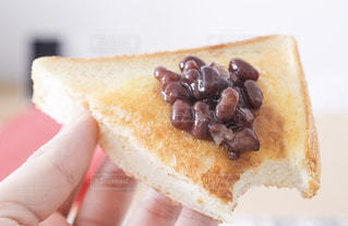 皿の上のケーキのスライスを持っている手の写真・画像素材[1148612]