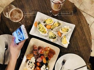 食品のプレートをテーブルに着席した人の写真・画像素材[1065942]