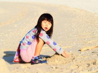 ビーチに座っている少女の写真・画像素材[1022103]