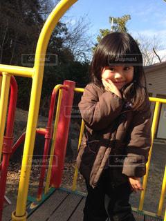 子供の遊び場の前で立っている女の子の写真・画像素材[1021348]