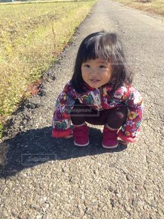 地面に座っている小さな女の子の写真・画像素材[1027346]