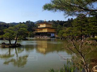 背景に金閣寺と木々 に囲まれた水の体中の小型船の写真・画像素材[1028053]