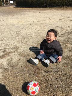 土の中に立っている小さな男の子の写真・画像素材[1028114]