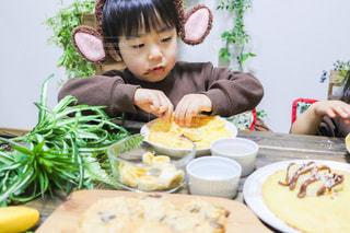 食べ物を食べるテーブルに座っている小さな男の子の写真・画像素材[3392405]