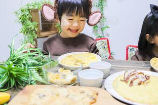 食べ物の皿を持ったテーブルに座っている小さな男の子の写真・画像素材[3392400]