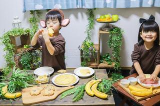 食べ物の皿を持ってテーブルに座っている女性の写真・画像素材[3392406]