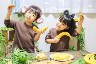 食べ物の皿を持ったテーブルに座っている小さな男の子の写真・画像素材[3392413]