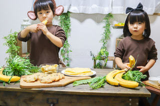 テーブルの上に座っている食べ物の束を抱いている小さな女の子の写真・画像素材[3392420]