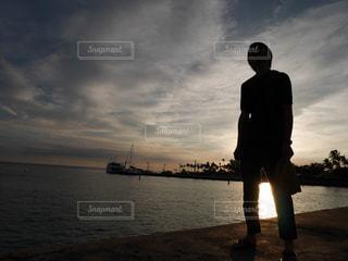 水の体の横に立っている人の写真・画像素材[1030353]