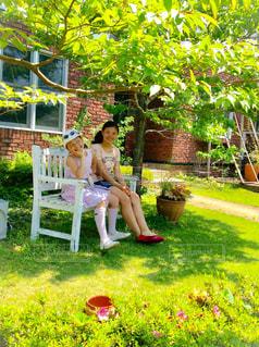 庭のベンチに座っている女の子の写真・画像素材[1041814]
