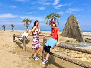 ビーチの砂の上に立っている少女の写真・画像素材[1051163]