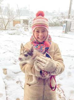 雪の中で犬を持っている人の写真・画像素材[1051374]