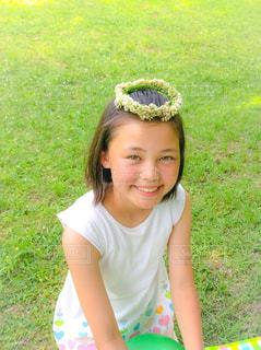 草の中に座っている少女の写真・画像素材[1051575]