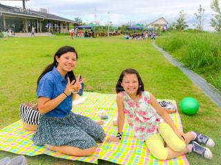 芝生に座っている少女の写真・画像素材[1051700]