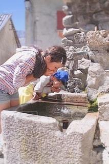 石造りの建物の前で水を飲む女の子の写真・画像素材[3458681]