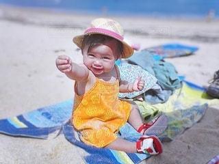 砂浜に座っている小さな女の子の写真・画像素材[3471576]