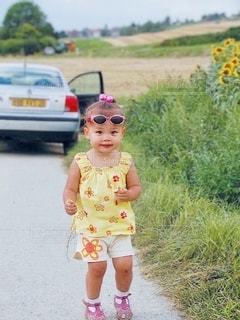 田舎道に立っている小さな女の子の写真・画像素材[3472109]