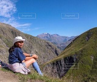 山の側に座っている女の子の写真・画像素材[3594511]