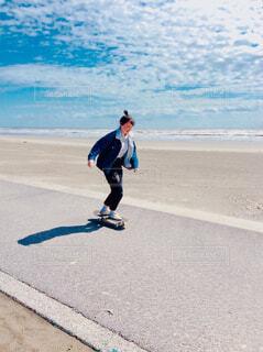 ビーチでスケボーに乗っている女の子の写真・画像素材[4373261]