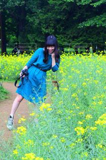 フィールドに黄色の花の人の写真・画像素材[1163958]