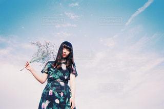 澄んだ青い空の前に立っている人の写真・画像素材[1234023]