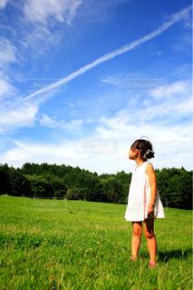 女の子と飛行機雲の写真・画像素材[1115863]
