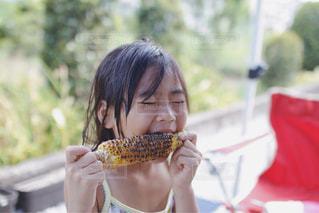とうもろこしを食べる女の子の写真・画像素材[1197276]