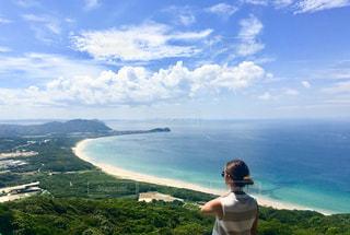 水体を見下ろす丘の上に立っている人の写真・画像素材[1033078]